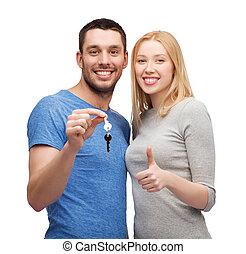 smil, par, holde, nøgler, og, viser, tommelfingre oppe