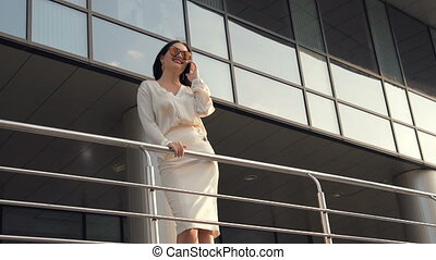 Smile and Success. Young woman talking by phone in front of...