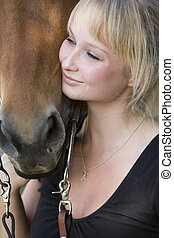 blond woman with her own brown horse