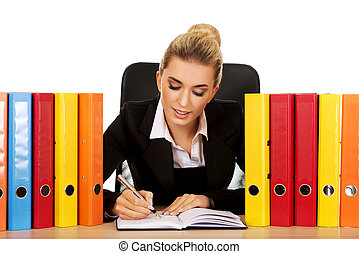Smile businesswoman with binders by a desk