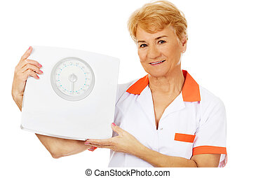 Smile elderly female doctor or nurse holds weigh scale
