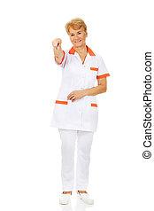Smile elderly female doctor or nurse pointing at camera