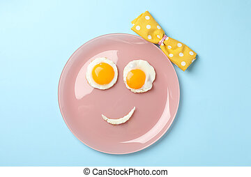 Smile face made of plate with fried eggs on blue background, top view
