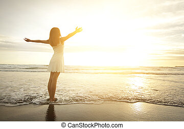 Smile Freedom and happiness woman on beach. She is enjoying serene ocean nature during travel holidays vacation outdoors. asian beauty