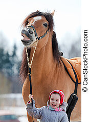 Smile of horse and child closeup in winter
