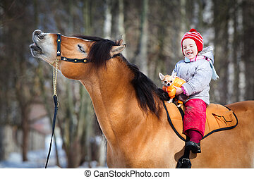 Smile of horse and child closeup in winter.