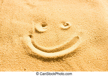 Smile sign drawing on the beach sand