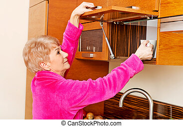Smile senior woman taking mug from a kitchen cabinet.