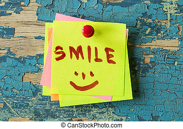 SMILE text written on sticky note on  wooden background