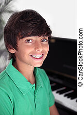 Closeup of kid with big smile wearing braces on his teeth. He is sitting at the piano.