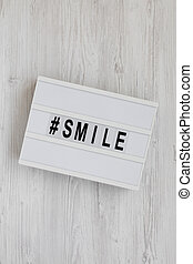 'Smile' word on a lightbox on a white wooden surface, top view. Flat lay, from above, overhead.