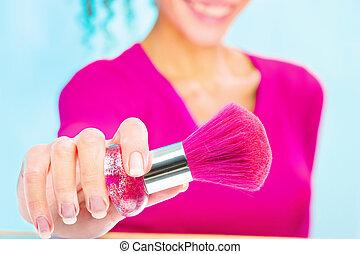 girl holding powder brush, focus on brush