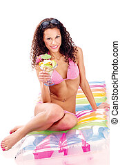 woman on air mattress holding cup of fruits