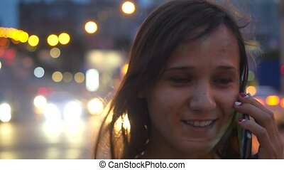 Smiles beautiful businesswoman talking by mobile phone in city at night street