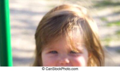 Smiley baby girl swingin on swing outdoor in the park