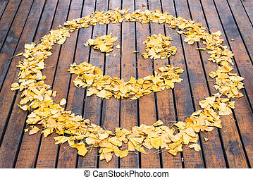 Smiley drawn with yellows leaves on a wooden ground