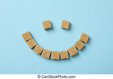 Smiley face made of sugar cubes on blue background, top view