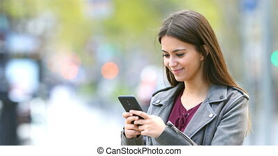 Smiley fashion teen texting on phone in the street