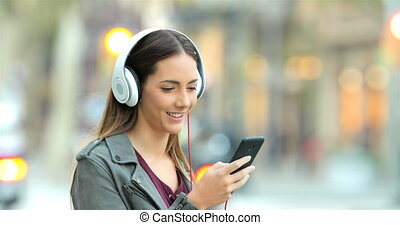 Smiley girl listening to music in the street