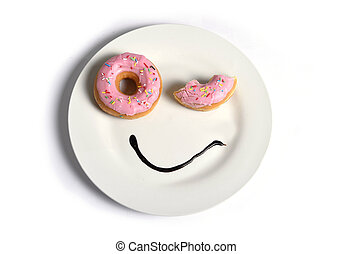 smiley happy face made on dish with donuts blinking eye and chocolate syrup as smile in sugar and sweet addiction