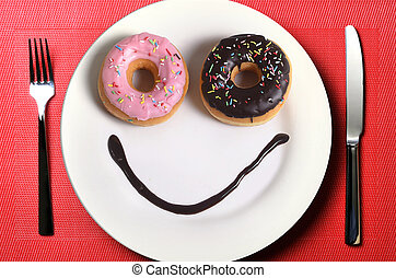 smiley happy face made on dish with donuts eyes and chocolate syrup as smile in sugar and sweet addiction nutrition