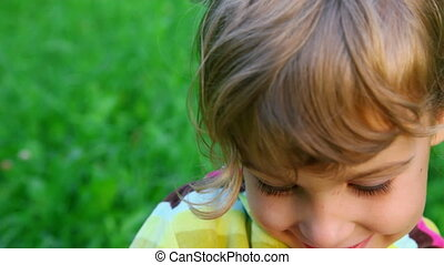smiley little girl on green grass background