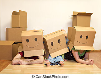 Smiley moving family concept - couple with a kid and lots of cardboard boxes