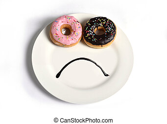 smiley sad face made on dish with donuts as eyes and chocolate syrup mouth in sugar sweet addiction diet and nutrition