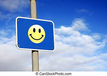 Smiley sign against a blue sky