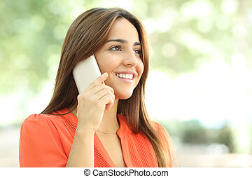 Smiley woman in orange talking on phone in a park