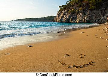 smiley written on sandy beach