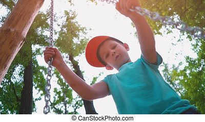 Smiling 5-year-old boy in a blue T-shirt and with a cap on his head swinging on a swing with steel chains, a child has fun on a children's swing surrounded by green trees, slow motion