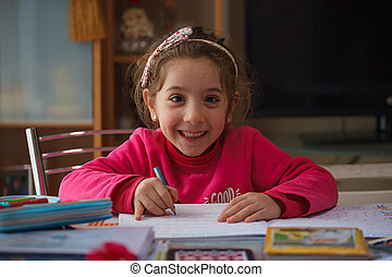 Smiling 6 year old girl does her homework
