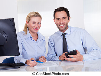 Smiling accountants discussing reports at the office