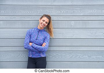 Smiling active woman standing with arms crossed