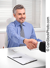 Smiling adult business man shaking hands. Close up of hand shake during successful negotiations