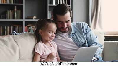 Smiling adult dad teaching kid daughter using laptop at home