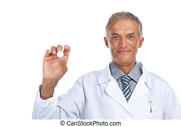Smiling  adult doctor holding white pill in hand. Close up isolated on white