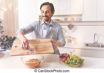 Smiling adult man cooking with inspiration