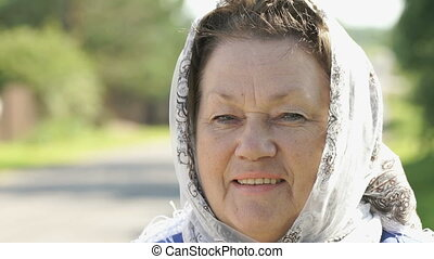 Smiling adult woman in white handkerchief outdoors