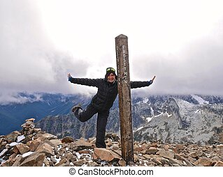 Smiling adult woman on mountain top, feeling happy and successful.