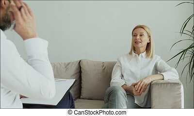 Smiling adult woman sitting on couch talking to male psychologist or psychoanalyst in office