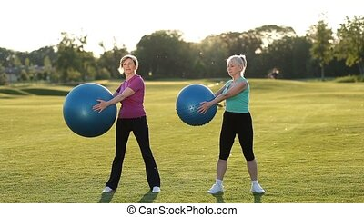 Smiling adult women doing ab exercises with balls