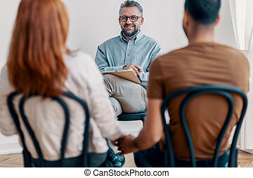 Smiling adviser for couple talking with young lovely marriage