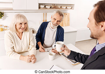 Smiling advisor enjoying conversation with aging couple of clients