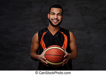 Smiling African-American basketball player in sportswear isolated over dark background.