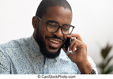 Smiling african american business man talking on smartphone consult client
