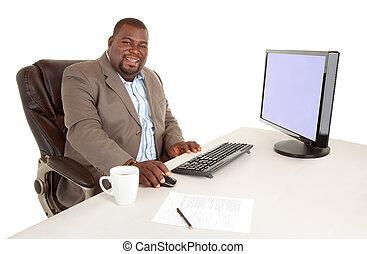 Smiling African American Businessman Sitting at Desk