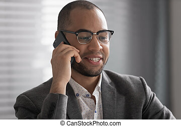 Smiling African American businessman talking on phone close up