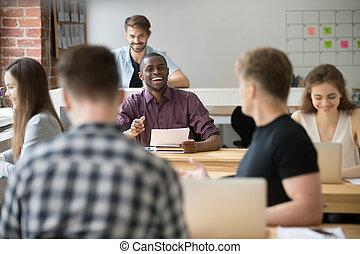 Smiling african-american businessman talking to colleague in cow
